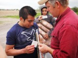 Migrant farm worker Victor Diaz receives a check for back pay from farmer Ray Brands.