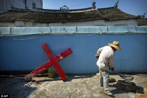 Hard work: A church member shovels cement mix while preparing to replace the Taitou Village Protestant church building's cross. [click on photo for story]