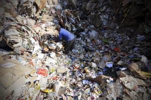 "A Coptic Christian man picks up trash before it is recycled inside Garbage City in Cairo. [Cairo's zabbaleen are primarily Coptic Christians, a sizable minority who have a history of being ostracized by Islamist powers in the country.] For more on Cairo's ""Town of Trash,"" please click on picture."