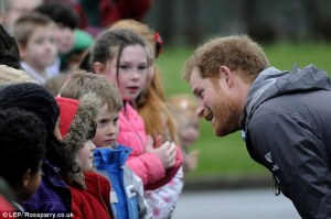Prince Harry happily takes the time to speak to some of the children individually and bends down to hear them.
